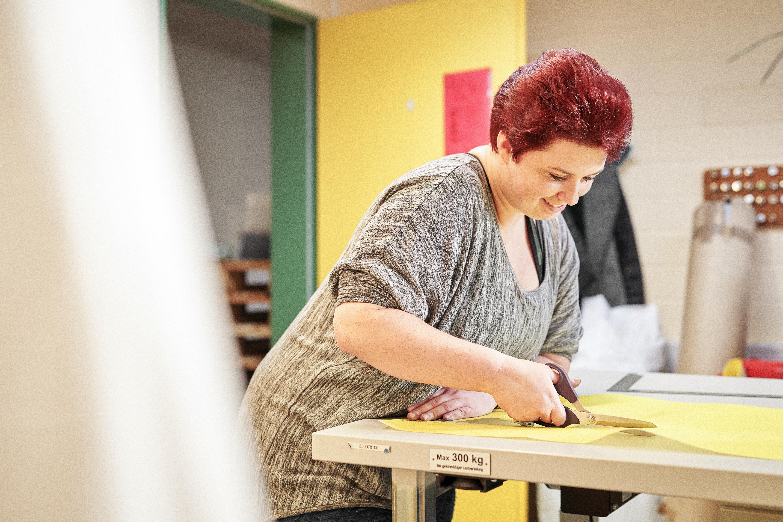 Eine Frau mit roten Haaren steht an einem Tisch und schneidet das gelbe Material für einen Bannerbeutel zu.